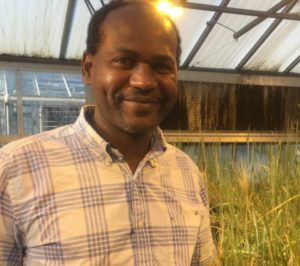 Sintayehu Daba smiling in the greenhouse after watering his wheat and barley plants