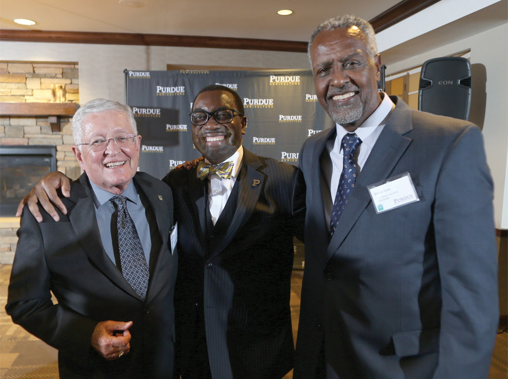 Purdue World Food Prize Laureates greet one another at the award ceremony: (l to r) Philip Nelson, Akinwumi Ayodeji Adesina, and Gebisa Ejeta