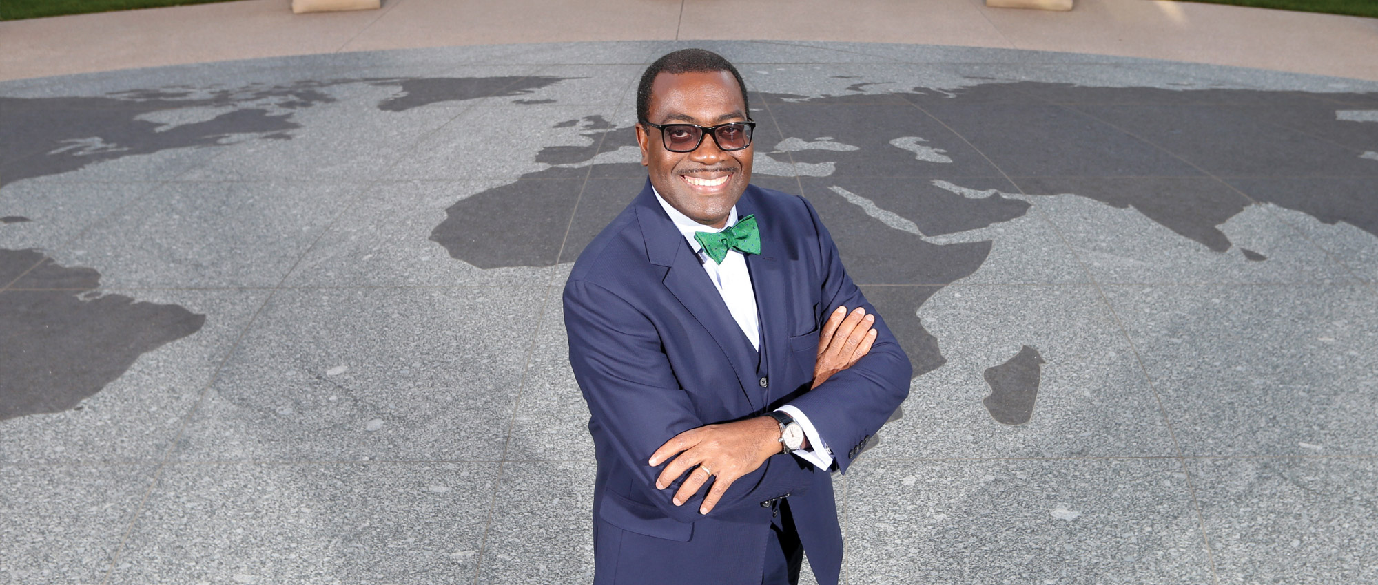 Akinwumi Ayodeji Adesina, president of the African Development Bank Group, stands with crossed arms on top of a stone world map