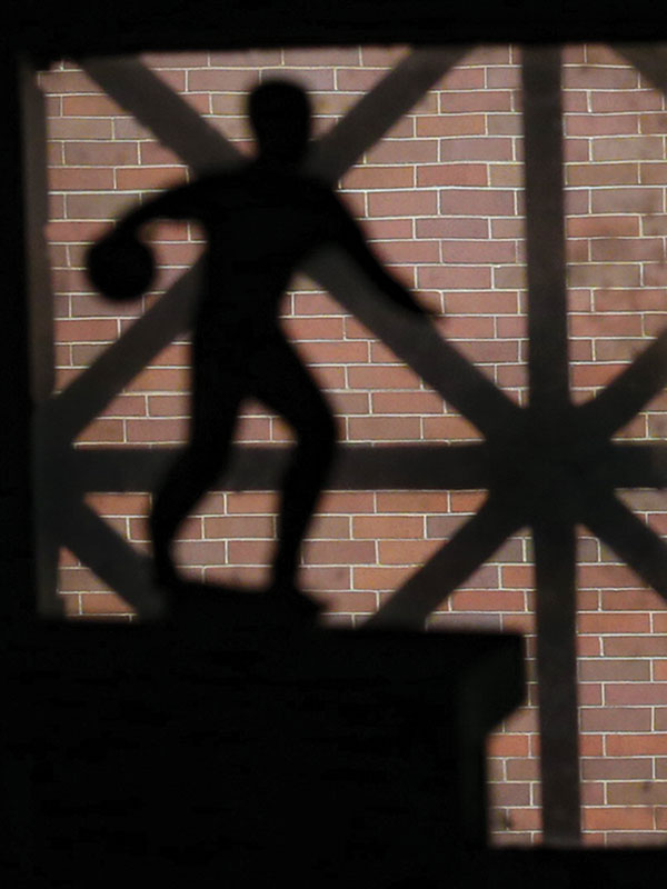 Shadow of bowling trophy cast against brick