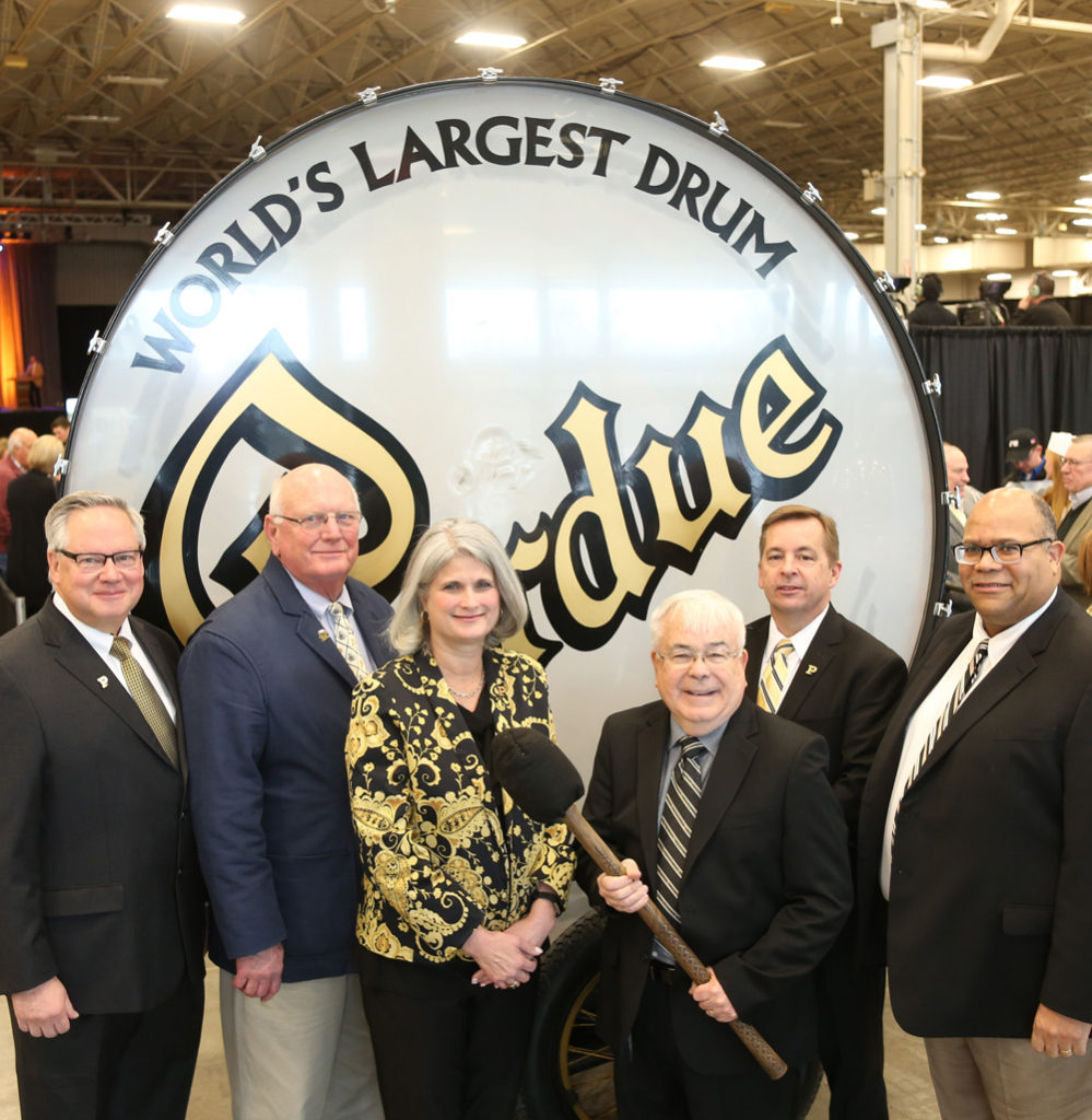 Certificate of Distinction Award Recipients Paul Marsh, John Frischie, Katherine Armstrong, Darrel Thomas, Ray Moistner, and James Monger, Jr. stand in front of the Purdue big bass drum