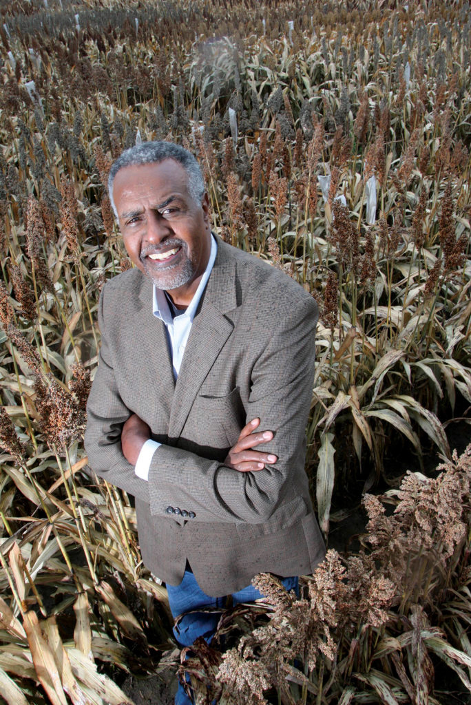Dr. Gebisa Ejeta stands in a field