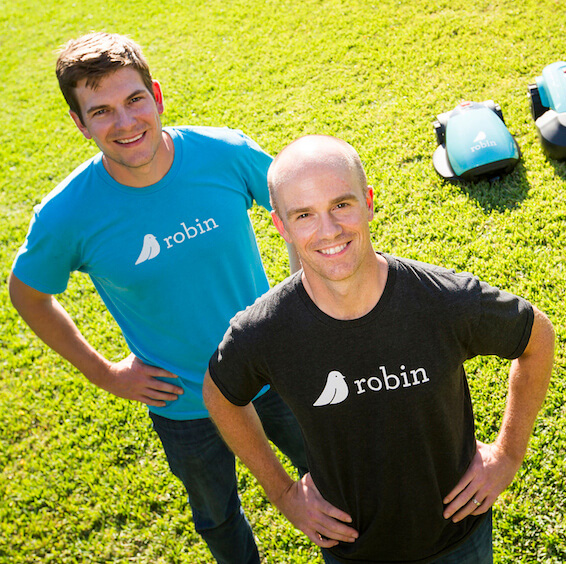 Bart Lomont and Justin Crandall stand in front of their robotic lawn mowers