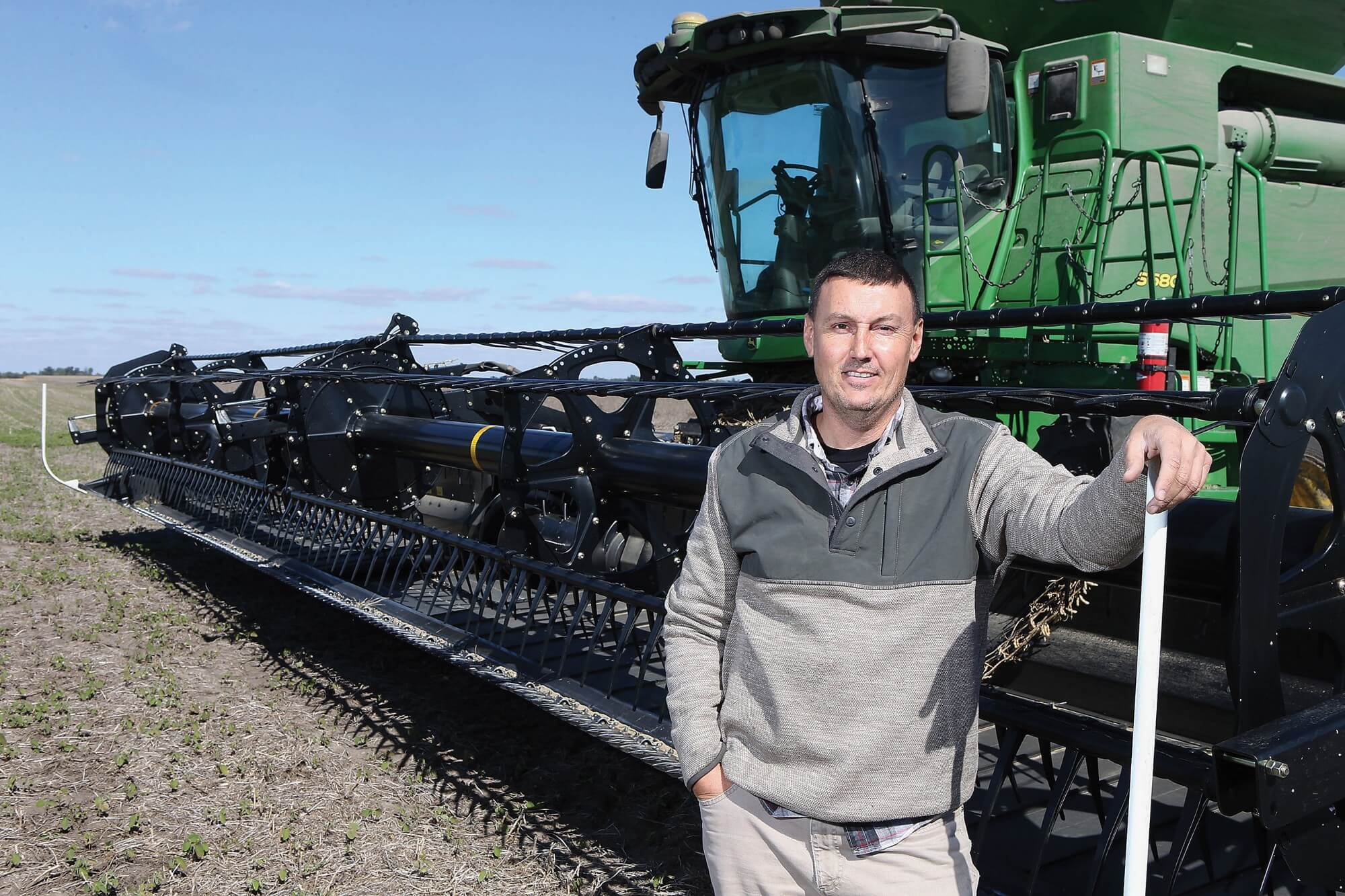 Brent Bible stands in front of a combine harvester in the field
