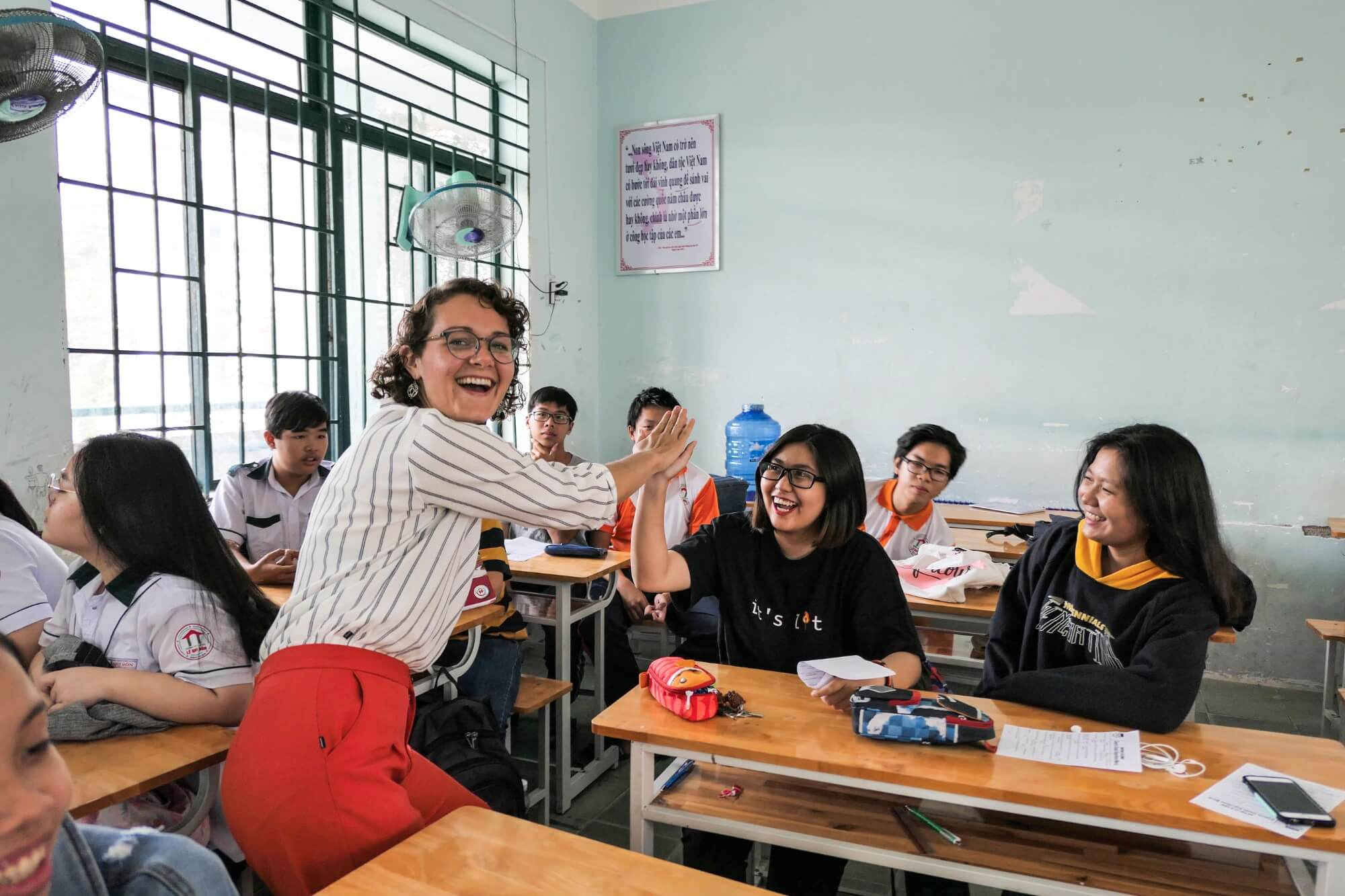 Chelsea Maupin high fives a student in a Vietnamese classroom