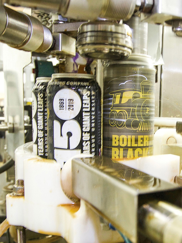beer being canned on machines at brewery