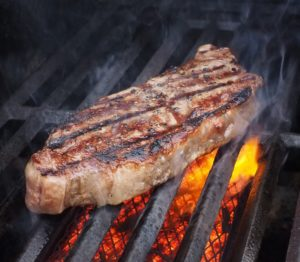 Pork chops over a hot grill.