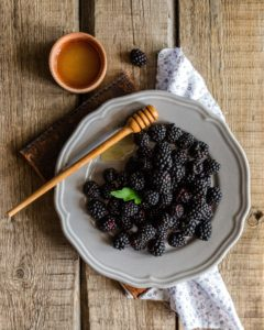 A bowl of blackberries sitting in honey.