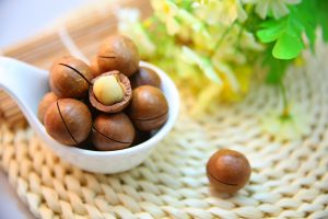 A spoon full of Macadamia nuts.