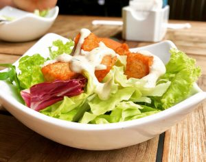 Salad with lettuce in a white bowl.