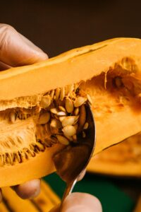 A picture of the seeds being scooped out of a squash.