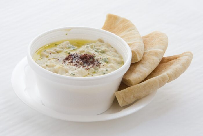 A container of hummus with peta bread.