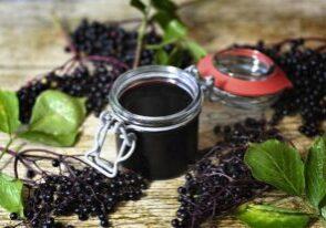 Elderberries and elderberry jam on a table.