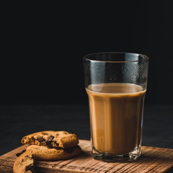 A glass of chocolate milk next to two cookies on a wooden board.