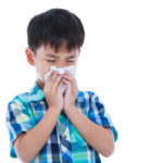 Asian boy using tissue to wipe snot. Isolated on white.