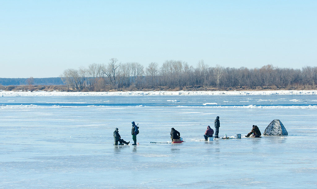 people ice fishing on a frozen lake