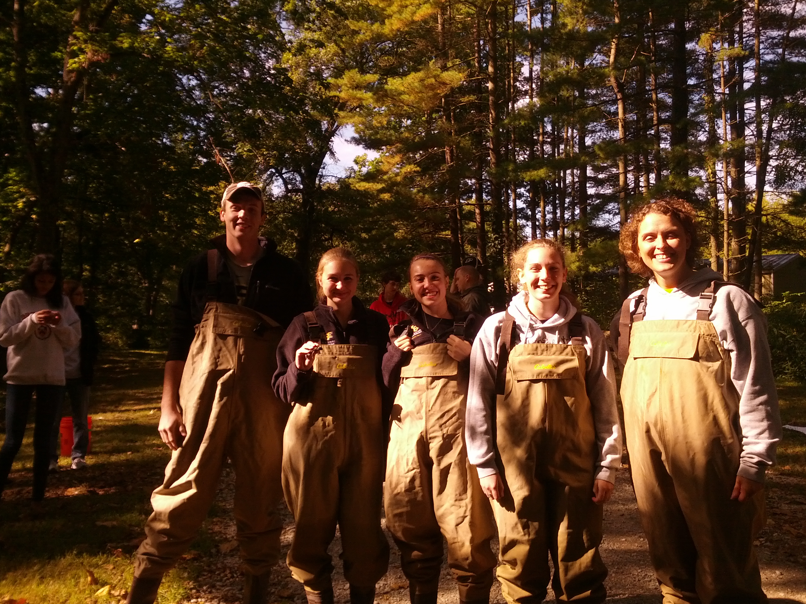 Students and advisor in waders.