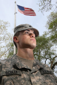 Ryan Scully in fatigues in front of US flag