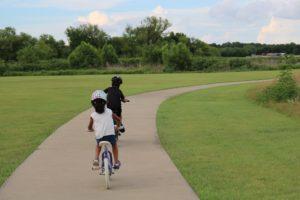 2 kids ride their bikes on a bike path