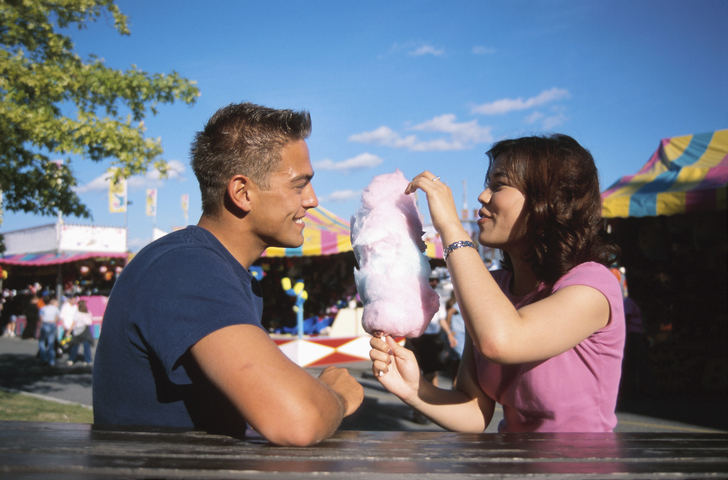 Couple sharing cotton candy at fair