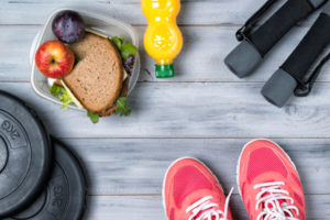 Fitness concept, pink sneakers, weight plates, dumbbells, sandwich, fruits and orange juice, wooden background, top view