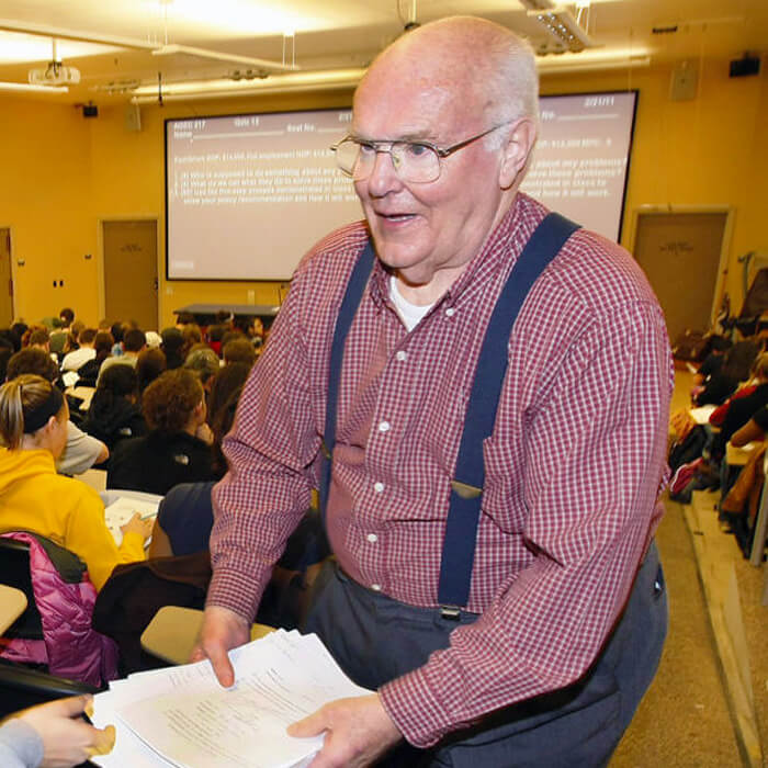 Bob Taylor distributes papers in his classroom