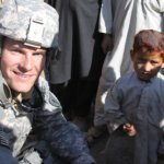 Bart Lomonth in uniform smiling with a child