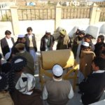 High school educators in the Future Farmers of Afghanistan seminar receive instruction on a barrel composter; part of an agricultural education kit that would soon be installed in their schools.