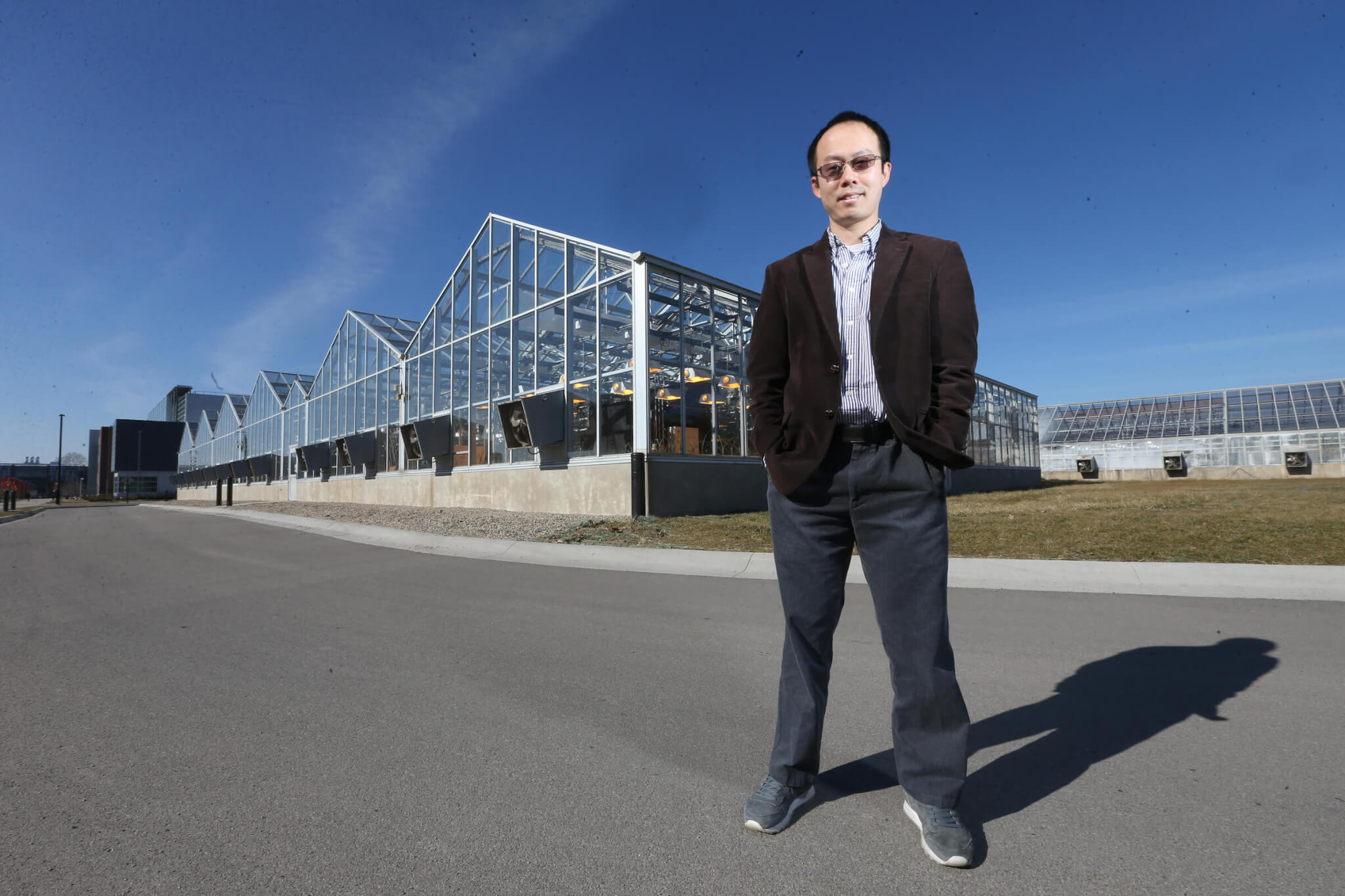 Jian Jin stands in front of greenhouses on Purdue's campus