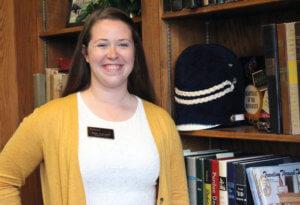 Sarah Voglewede standing near bookshelf
