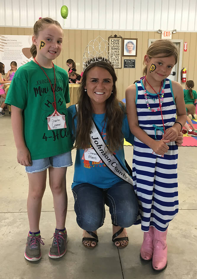 Samantha Morris with wearing her fair queen sash with two young students