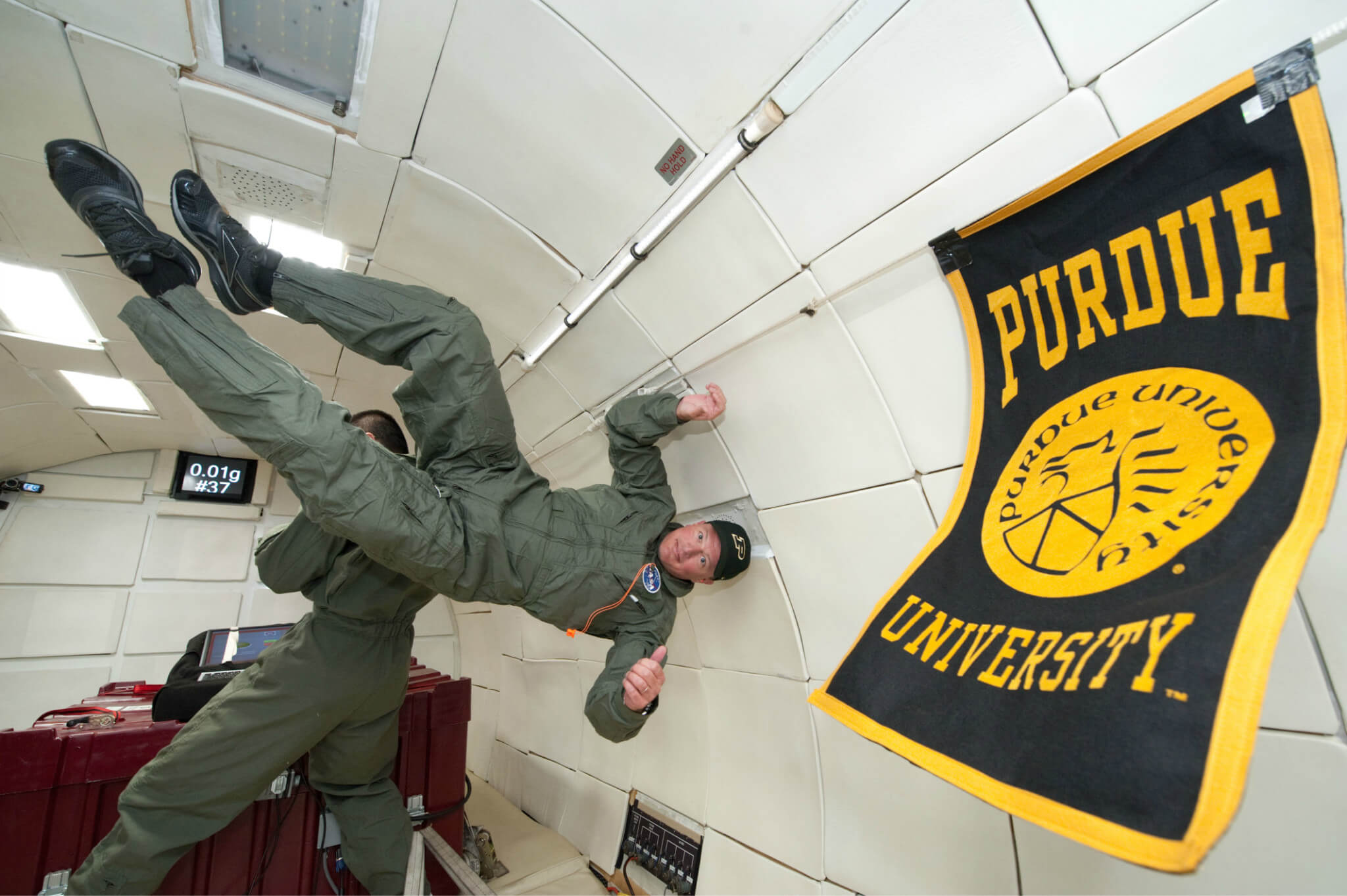 Weightless upside-down wearing Purdue hat next to Purdue flag