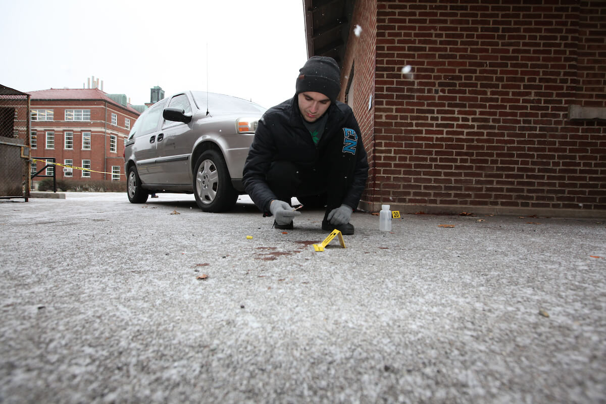 Student investigates the ground at a test crime scene in the snow