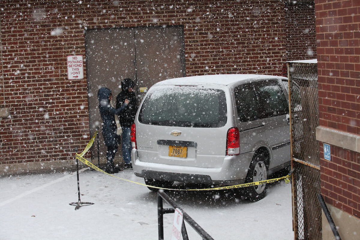 Students investigate an example crime scene in the snow with a van