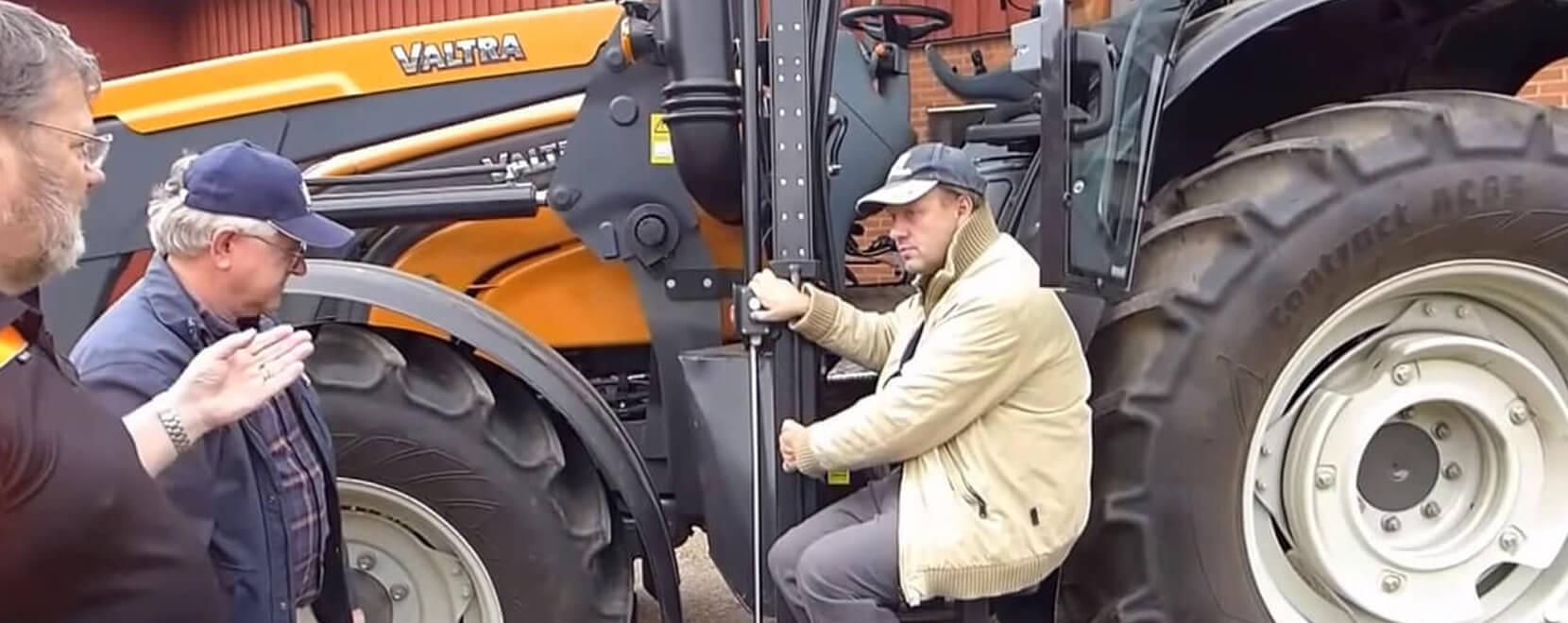 Men speaking in front of a tractor