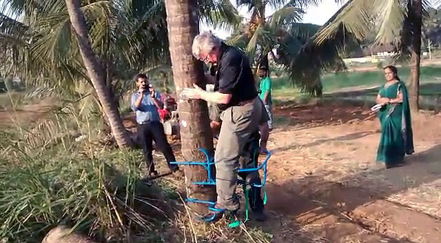 Bill Field tries out an assistive device for climbing palm trees in India. Field's work with adaptive technologies has taken him all around the world.