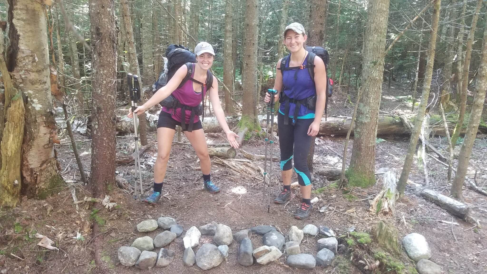 Rebekah and Baleigh smile with rocks marking 2000 miles