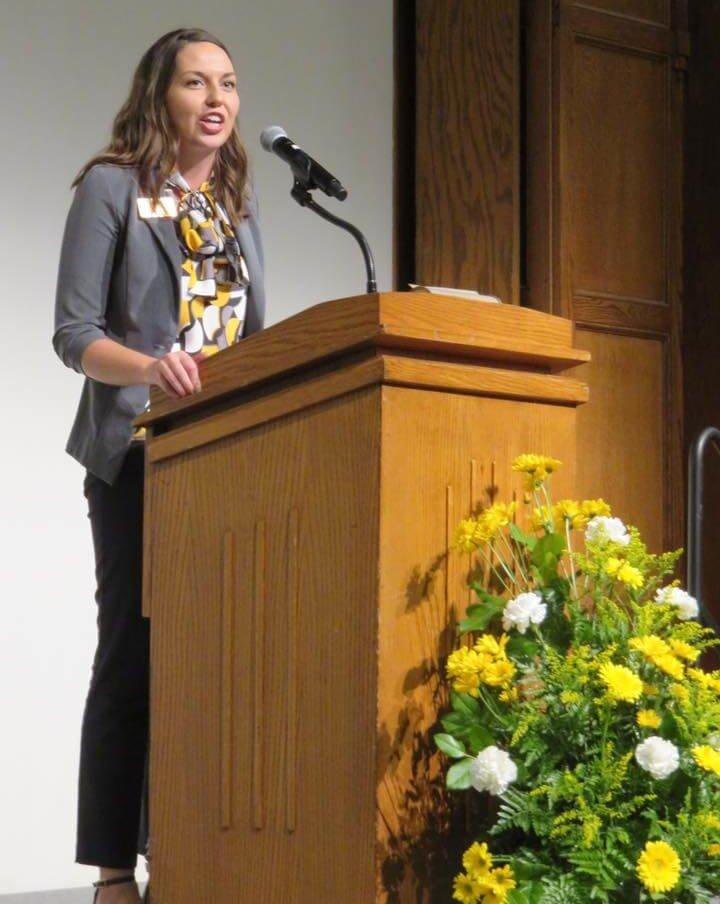 Cameron Mann speaking at a podium