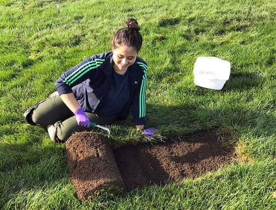 Marian on the ground with grass sod