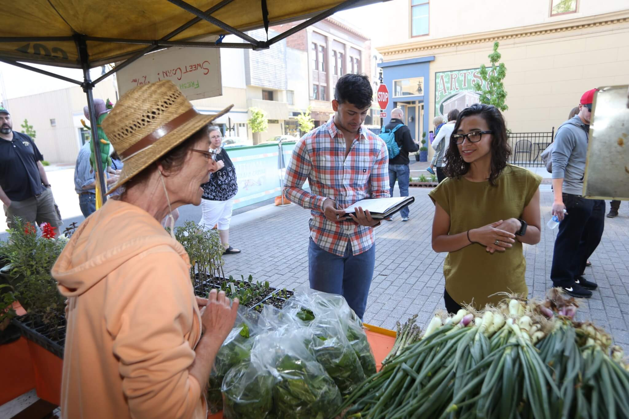 Ariana Torres speaks with a farmer at the Lafayette Farmers Market pre-COVID-19.