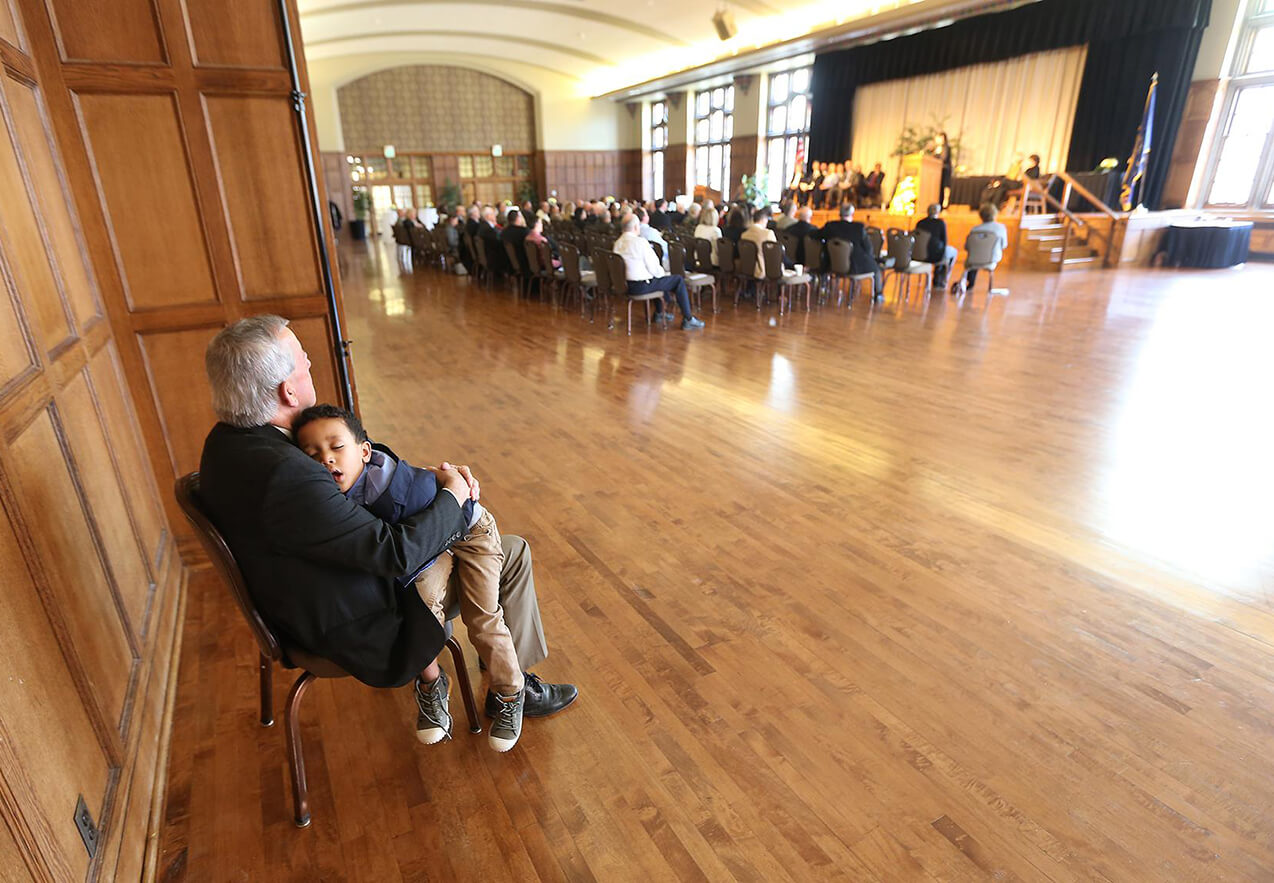 Mark Russell can include babysitting duties on his Purdue resume. During the Distinguished Ag Alumni event in 2018, Russell held a napping David Steiner so the rest of the Steiner family could enjoy the ceremony in the Purdue Memorial Union. David's dad, Eric, was a 2018 honoree and a former student of Russell.  Photo by Tom Campbell.