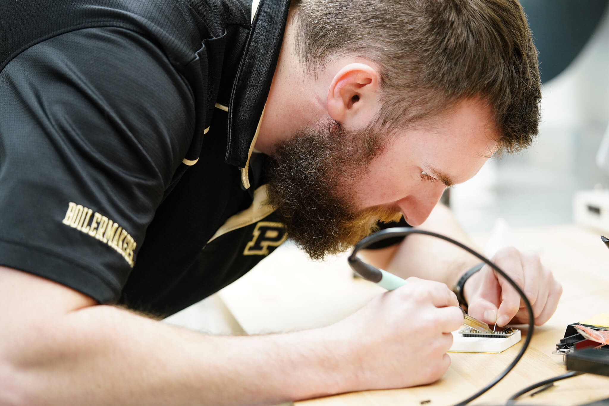 Aaron Etienne solders a small circuit board as part of a data acquisition project.
